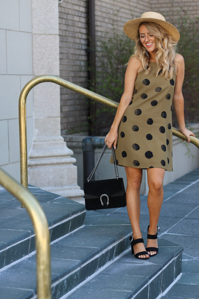 Amber is wearing a olive colored  polka dot shift dress