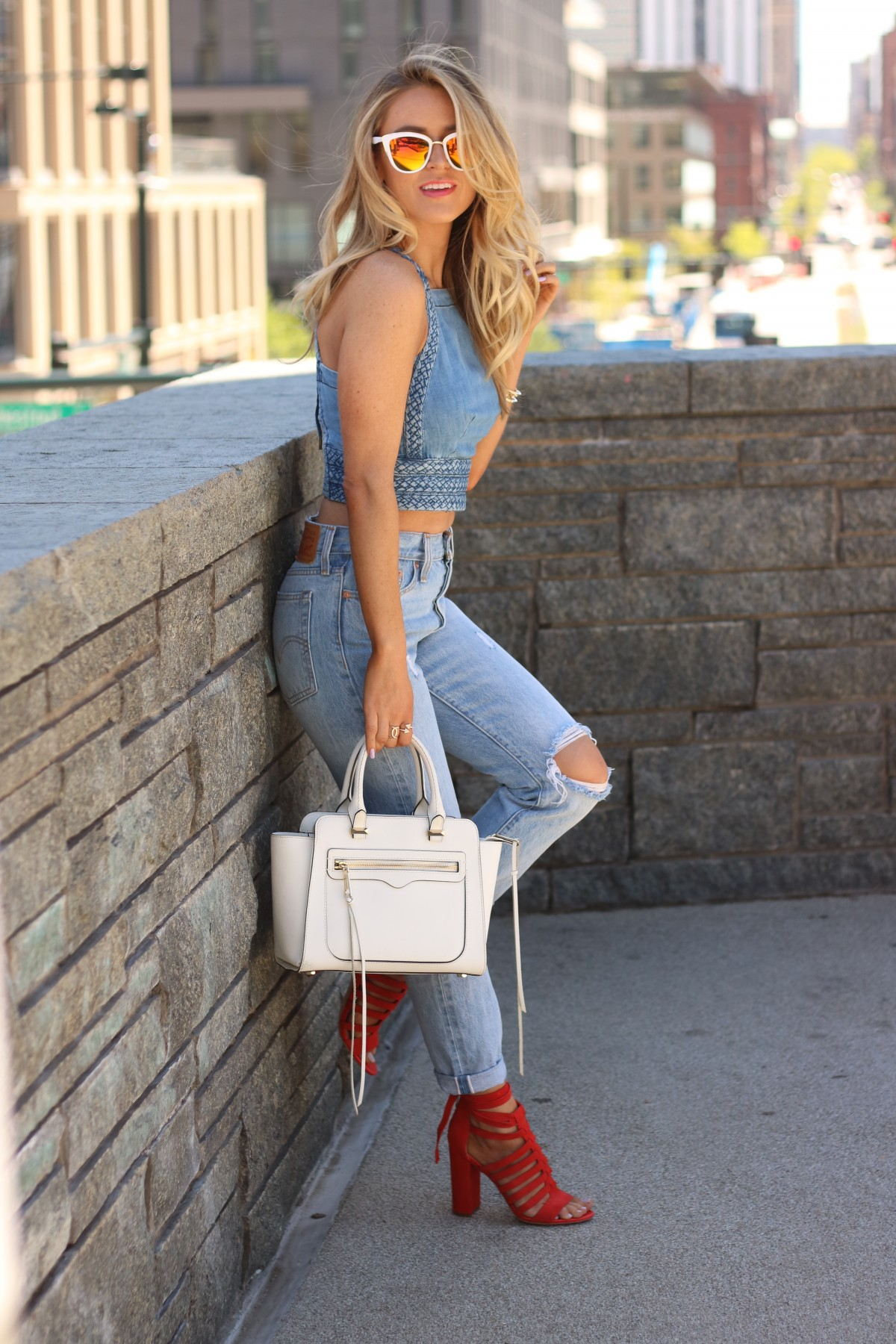  amber from every once in a style wearing   Le Spec sunglasses   denim on denim   white satchel