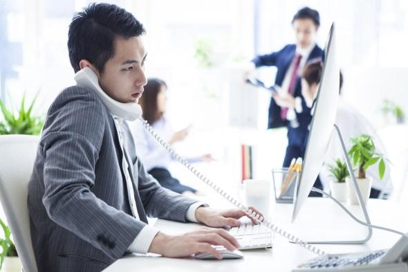 英語で電話応対をするビジネスマン