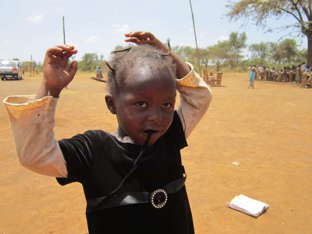 a dusty schoolyard shows in this child's hair in Kampi Ya Moto