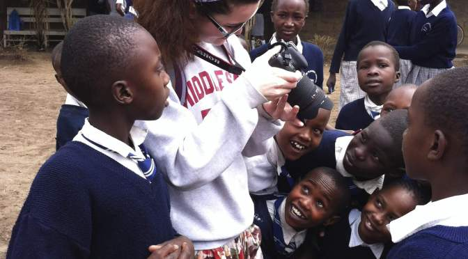 an American student showing her camera to Kenyan students