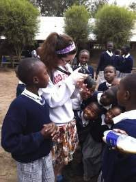 Autumn from Vermont shows her camera to students in Kiti