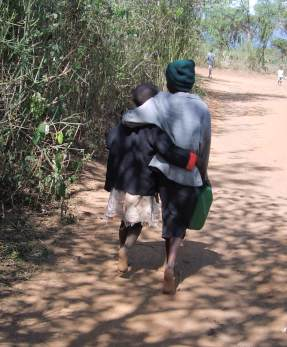 Two Kenyan children walking arm in arm providing for needs