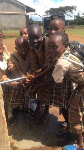 Kenyan school children getting maji (water) from a faucet