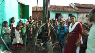 Children and adults Waiting by the drill for water in Orissa, India