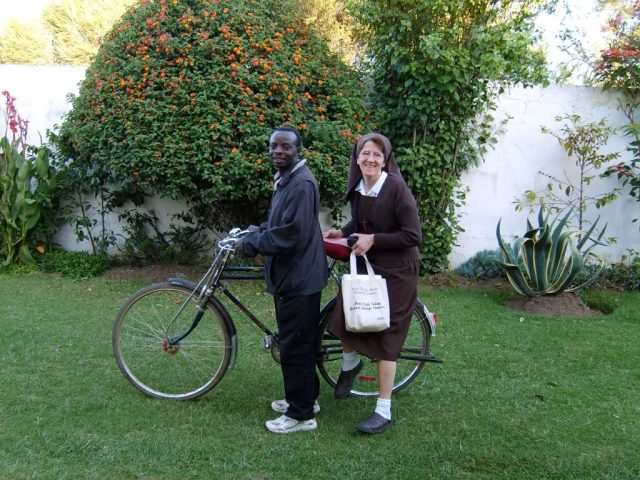 Ruth on the back of a bicycle in Kenya