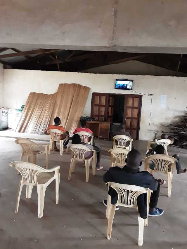 7 students watching lessons on a tv in Kenya.  Every day students come to William's church to watch lessons on a 32 inch screen