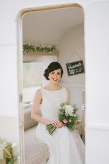 Stunning bride poses for the camera in the little creative caravan photo booth