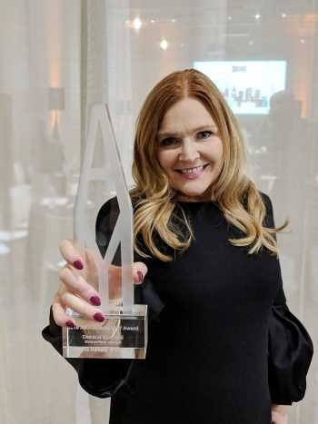 Danica Kombol holding Amy's 2019 Marketer of the Year trophy