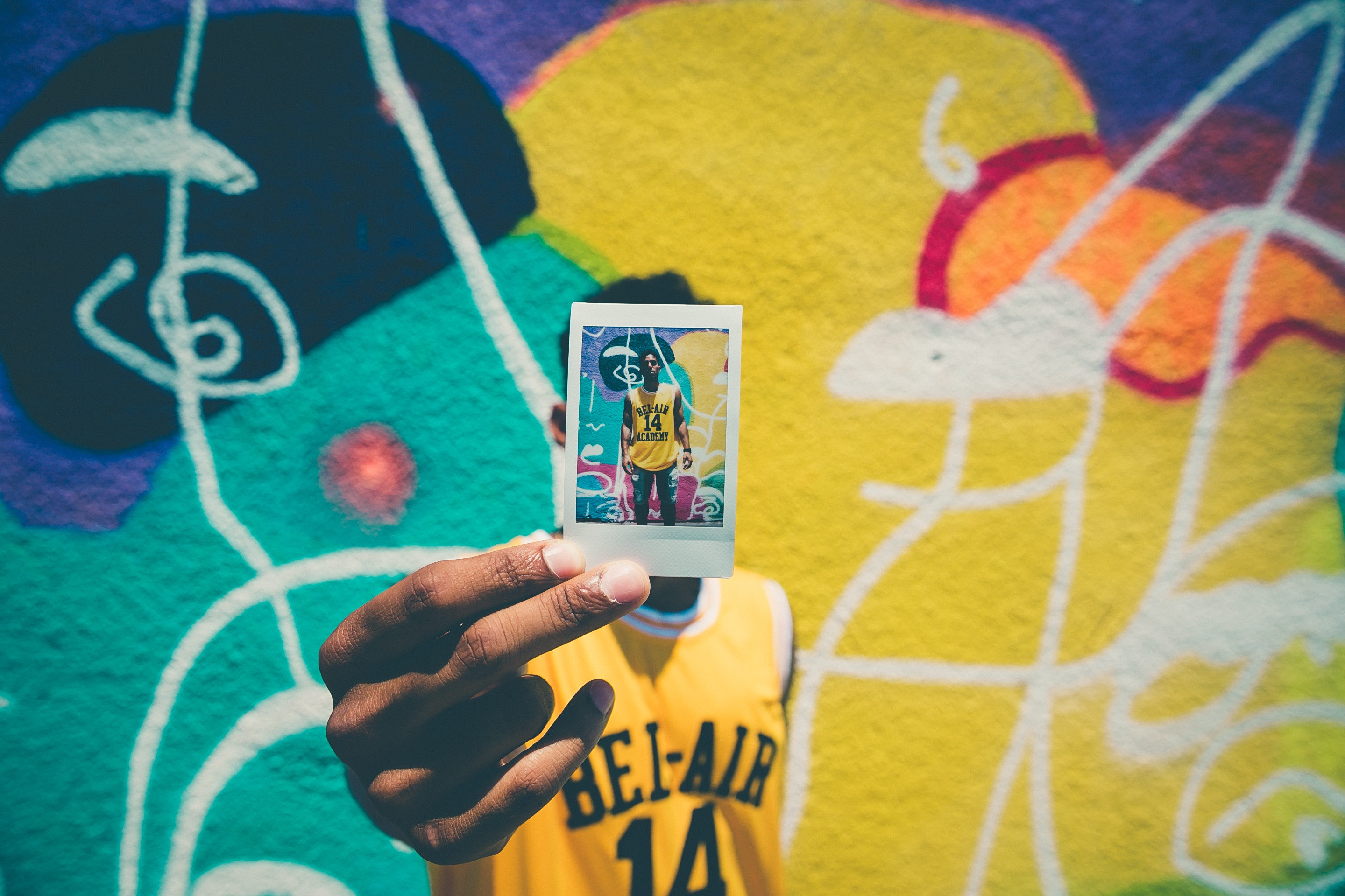 man displaying photo of himself in front of a colorful background