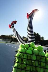 Image of a pair of upside down legs sticking out of a basket of tennis balls.