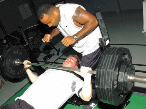 Man doing barbell bench press exercise