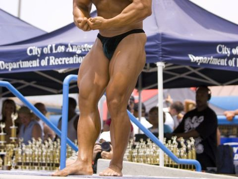 bodybuilder posing with leg muscle