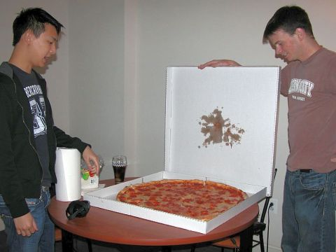 two young men with a very large pizza
