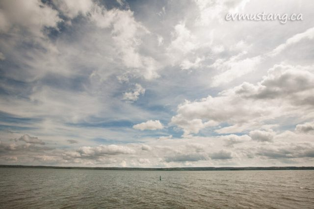 image of a lone buoy on rice lake under a sky layered with white cloud