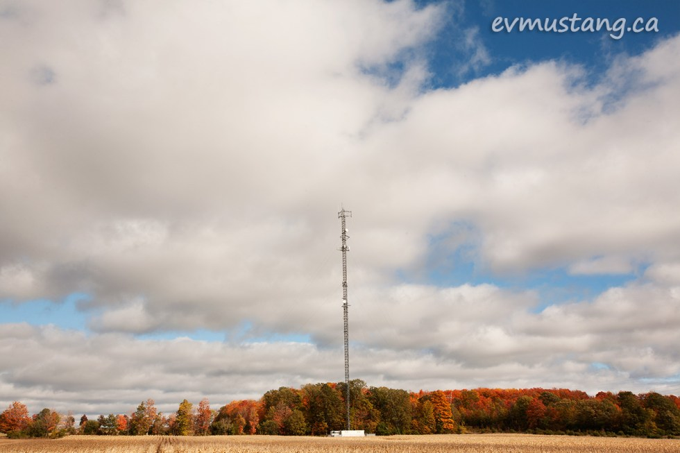 image of a cell tower against a cloudy blue sky and fall coloured trees across a wheat field
