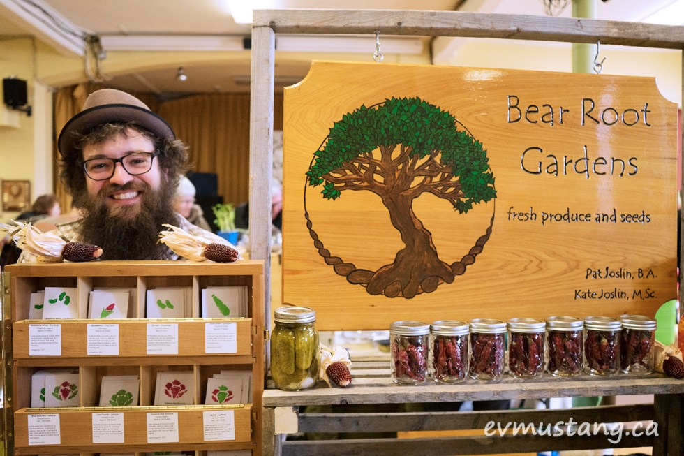 image of the owner of bear root garden standing behind their booth at peterborough's seedy sunday seed exchange