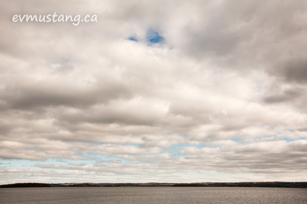 ima\ge of the south shore of rice lake with clouds breaking up in the distance showing patches of blue and hints of fall colour in the trees
