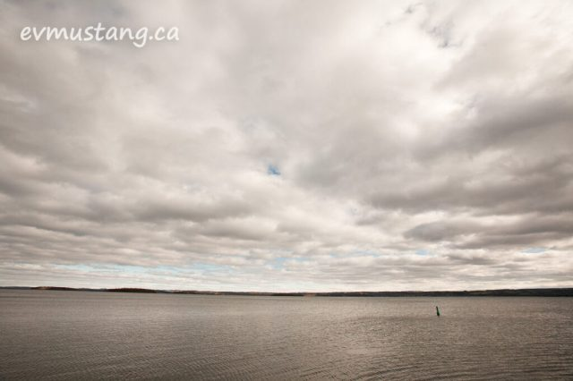 image of the south short of rice lake with sweeping clouds and patches of blue above and a single buoy in the foreground