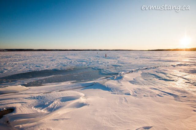 image of crack in the ice covering a lake with blue sky above and hint of orange on the horizon as the sun sinks