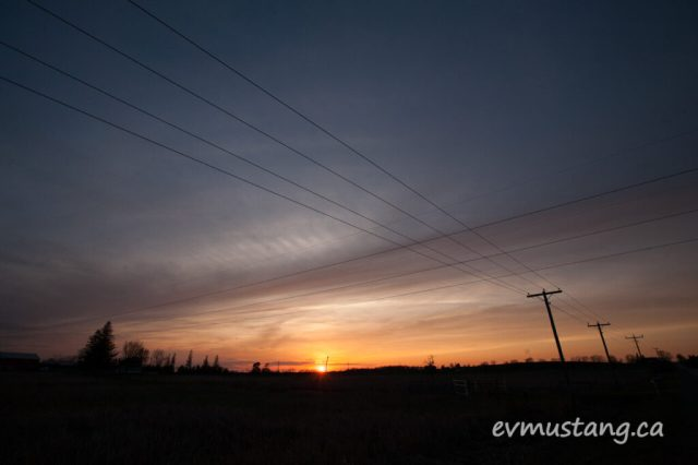 image of a deep orange and purple sunset over the silhouette of a farm field