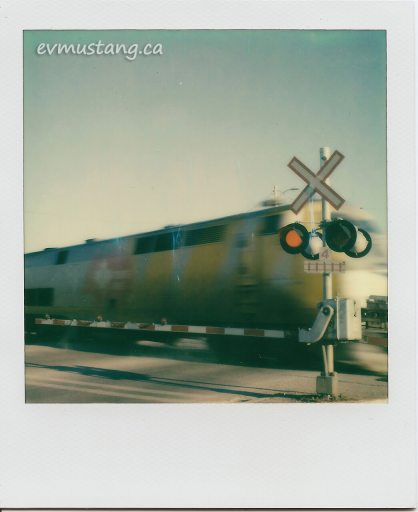 scan of a polaroid of a blur of a via rail train passing by a warning arm with the lights and bells clanging