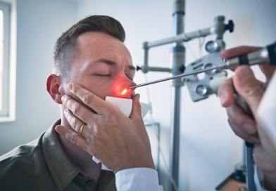Doctor doing nose examination of young patient