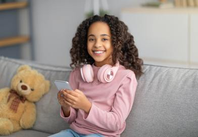 Online chat. Cheerful black girl using celphone with headphones on neck