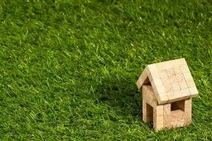 Buying your first home like this wooden model on a lawn