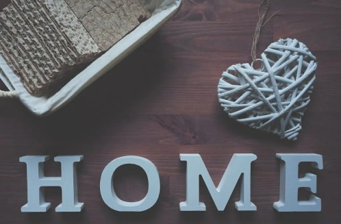 Four letters that spell the word ''home'' and a heart-shaped ornament on a wooden surface