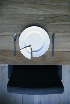 A broken plate, a knife and a fork on a wooden table
