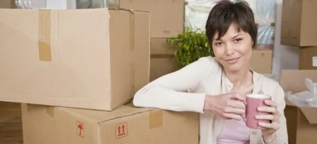 Woman with coffee sitting by moving boxes