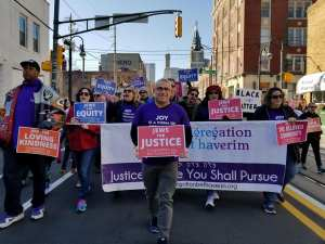"""Congregation Bet Haverim members marching with signs reading """"Jews for Justice,"""" """"Jews for Equity,"""" etc."""