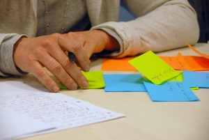 person's hands on table, with paper and post-its