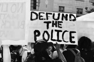"""protestors holding sign reading """"Defund the Police"""""""