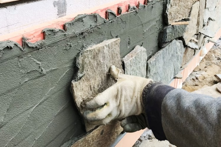 close up of person placing stone on wall on top of mortar