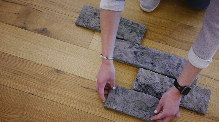 close up of person laying stone veneer down on the grown to visualize pattern