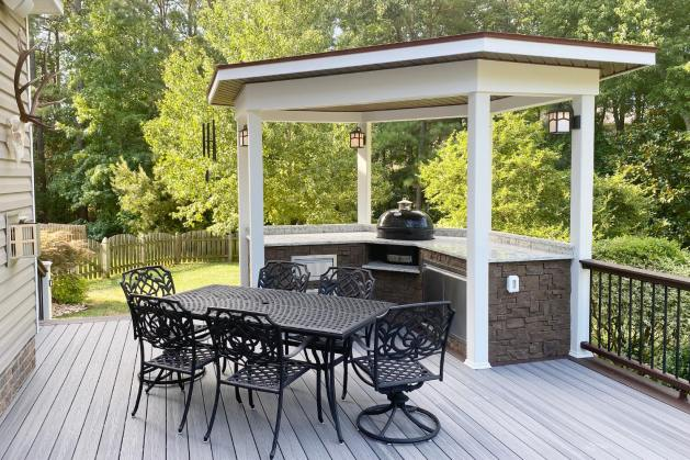 backyard patio with small white outdoor kitchen area with brown mortarless stone veneer accents