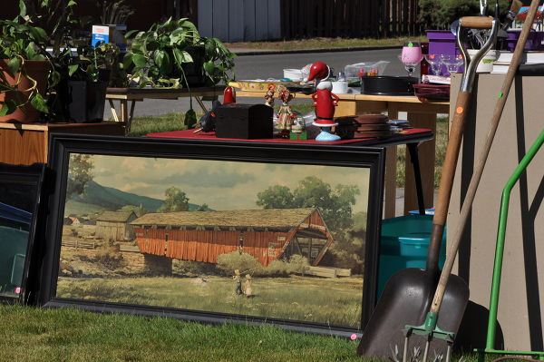 Large painting surround by stuff in yard sale before downsizing into an RV to travel the country.