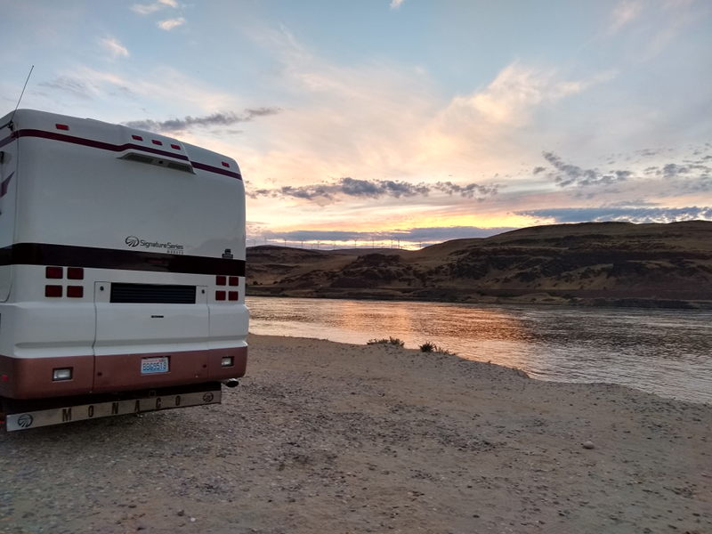The rear of the RV with an gorgeous sunset and the windmills up on the hill in the background.
