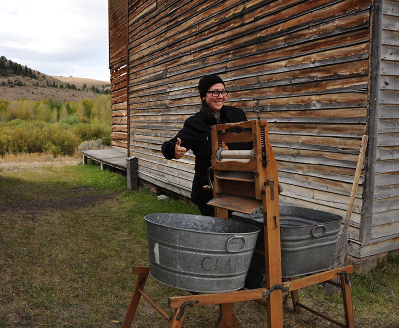 Adrianne showing what a washing machine in the 1860's looked like while touring the ghost town of Bannack.