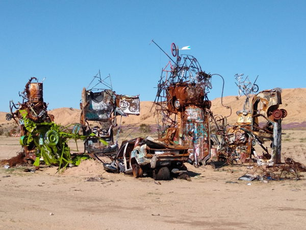 Old car parts and junk made into some sort of art, but looks like a pile of garbage.