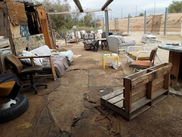 Image inside of the Slab City library showing very broken down furniture and a fence made of trash.