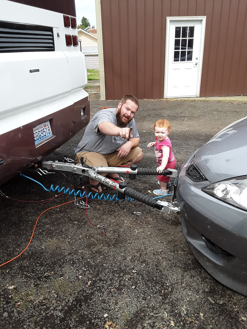 Chloe helping Adam hook up the car to the RV before hitting the road full time again.
