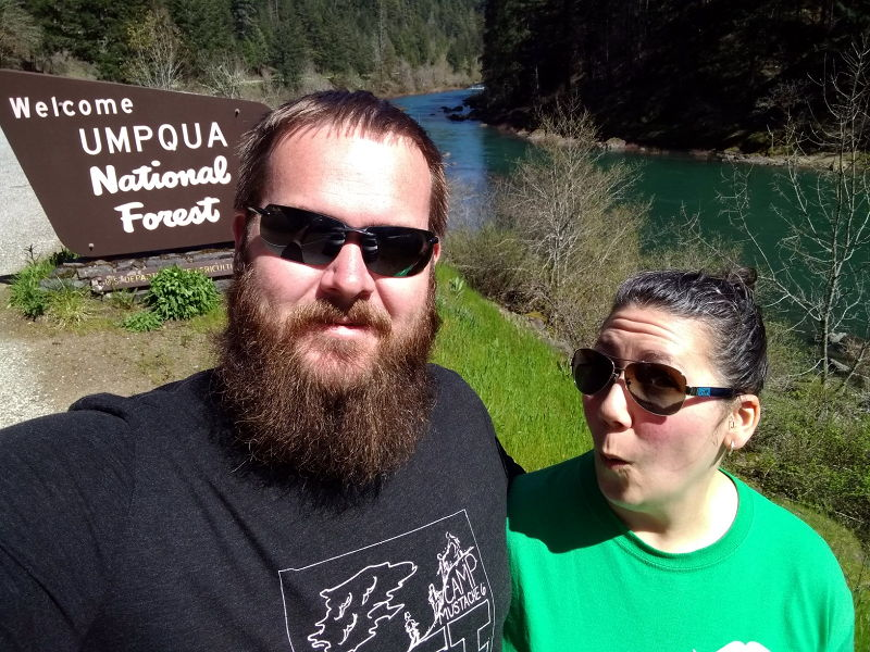 Adrianne and I standing next to the Umpqua National Forest sign with the North Umpqua river in the background.