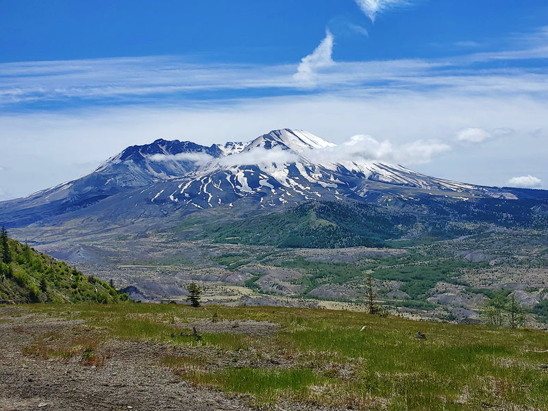 Mt St. Helens with a few clouds hovering over it.