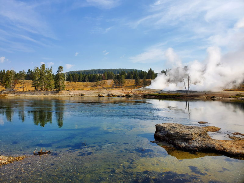 River in Yellowstone with steam rising from geyer in background.
