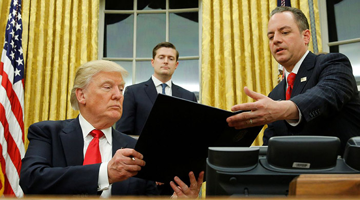 Trump hands Priebus an executive order that directs agencies to ease the burden of Obamacare, after signing it in the Oval Office in Washington