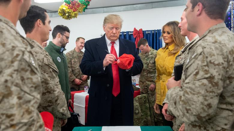 US President Donald Trump signs a hat as First Lady Melania Trump looks on as they greet members of the US military during an unannounced trip to Al Asad Air Base in Iraq on December 26, 2018. - President Donald Trump arrived in Iraq on his first visit to US troops deployed in a war zone since his election two years ago (Photo by SAUL LOEB / AFP) (Photo credit should read SAUL LOEB/AFP/Getty Images)