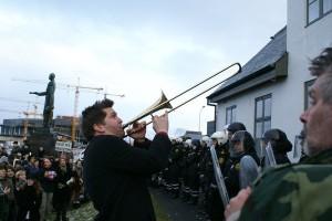 Музикант под прозорците на министър председателя по време на протестите срещу изплащането на задълженията на банките в Исландия през 2009. Creative Commons: OddurBen/Wikimedia Commons/.